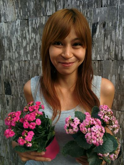 Portrait of smiling young woman holding flower pots against wooden wall