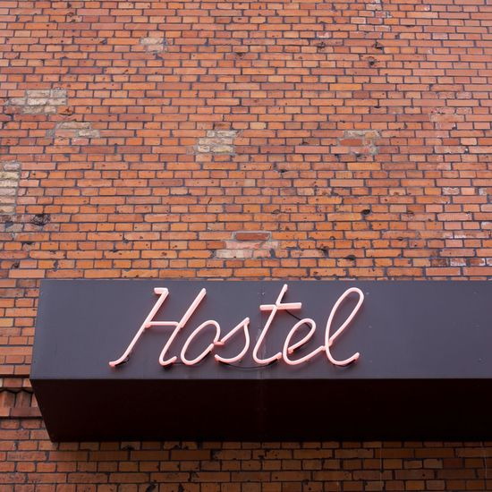 Low angle view of neon hostel sign on brick wall