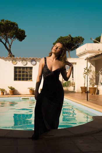 Woman standing by swimming pool
