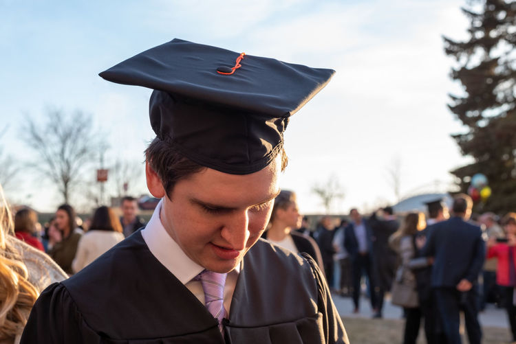 Close-up of young man wearing graduation gown against sky