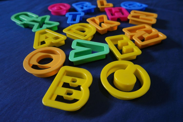 High angle view of multi colored alphabets on table
