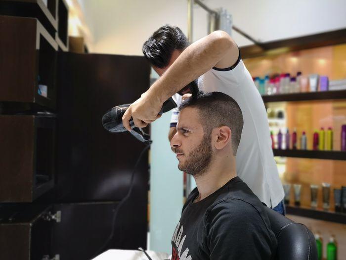 Barber cutting man hair in salon