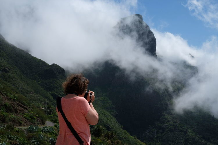 Rear view of woman photographing while standing on mountain