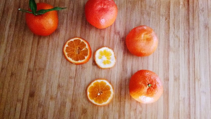 The orange fruit is on a wooden background. EyeEm Selects Fruit Healthy Eating Freshness Food And Drink Food Table Indoors  Cross Section No People Citrus Fruit SLICE Blood Orange Close-up Directly Above Sweet Food Ready-to-eat High Angle View