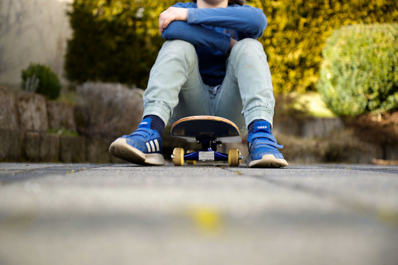 Low section of boy sitting on skateboard