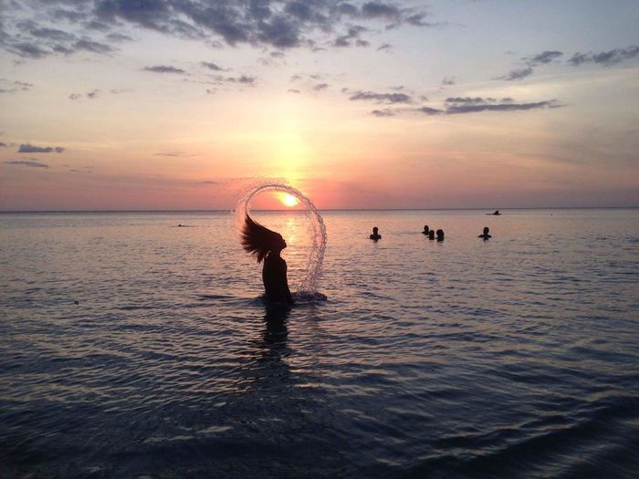 Side view of silhouette woman tossing hair in the sea