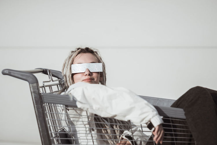 Young woman with dreadlocks sitting in shopping cart against wall