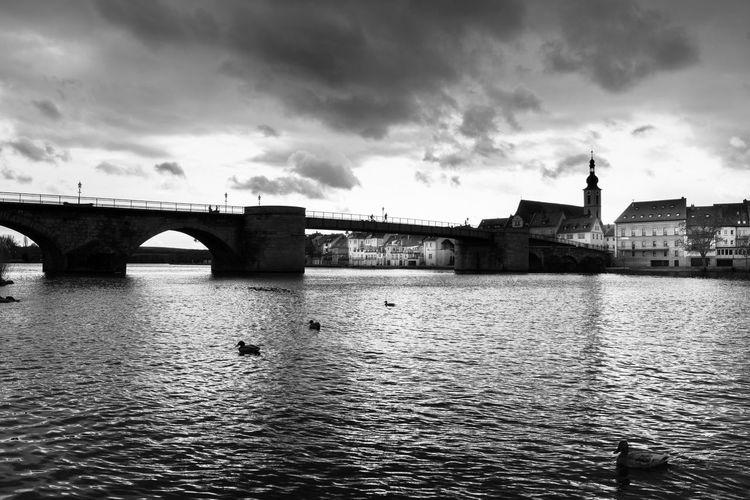 Bridge over river against cloudy sky