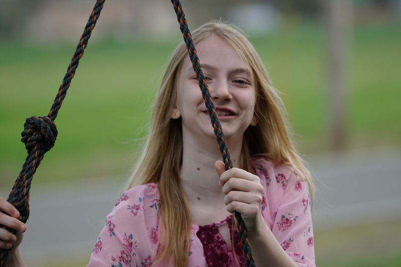 Portrait of girl holding swing rope
