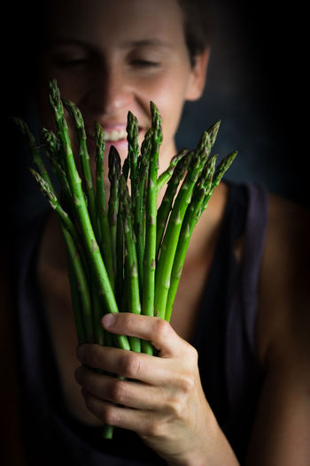Close-up of smiling woman holding asparagus at home