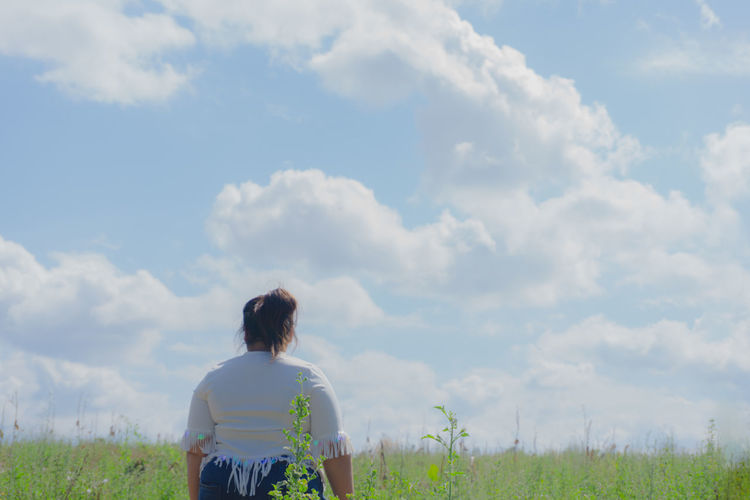 Rear view of young woman standing on grassy field against cloudy sky