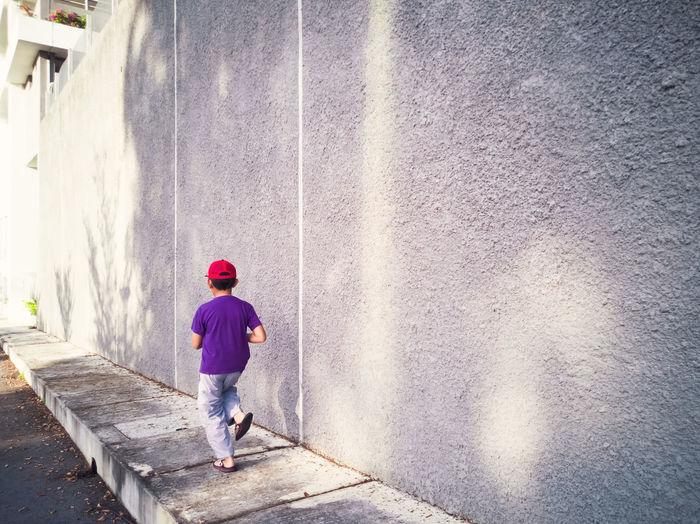 Rear view of boy walking on footpath by wall