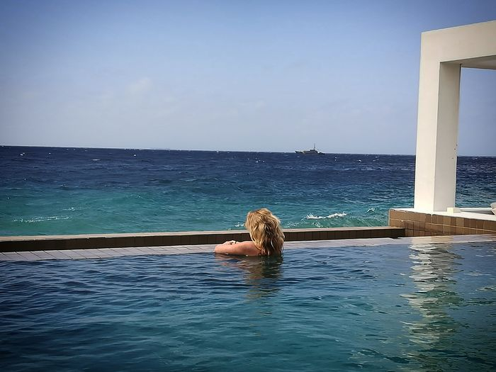 Rear view of woman looking at sea in swimming pool