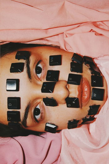 Portrait of woman with computer keys on face