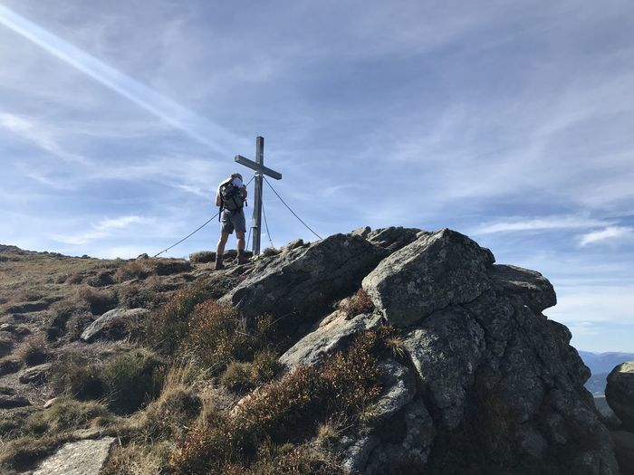 Rear view of man standing by religious cross on rock against sky