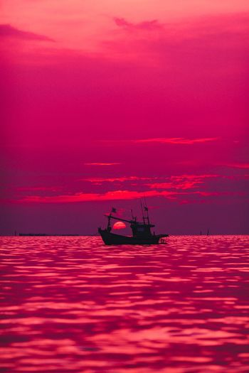 Silhouette of fishing boat on sea against sky during sunset