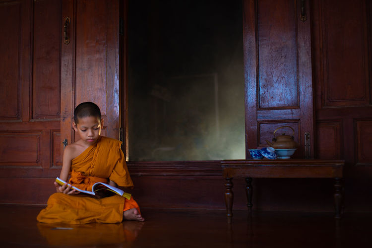 Full length of boy wearing traditional clothing reading book while sitting on floor
