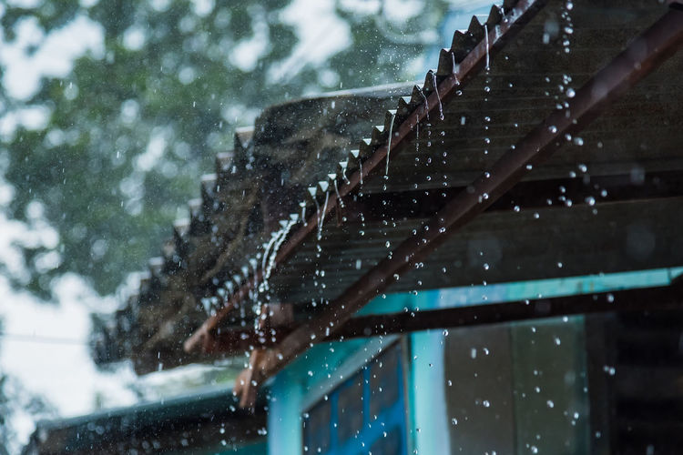 Low angle view of raindrops on roof of building during winter