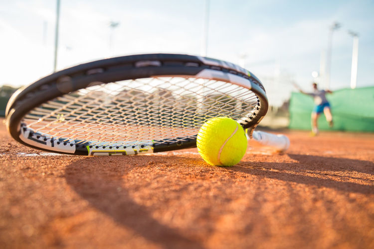 Close-up tennis racket and ball placed on court ground while player hitting ball. Athletics Court Field Green Recreation  Sunny Activity Ball Close-up Competition Equipment Fitness Floor Game Ground Hitting Individual Leisure person Player Racket Racquet Sport Summer Tennis 🎾
