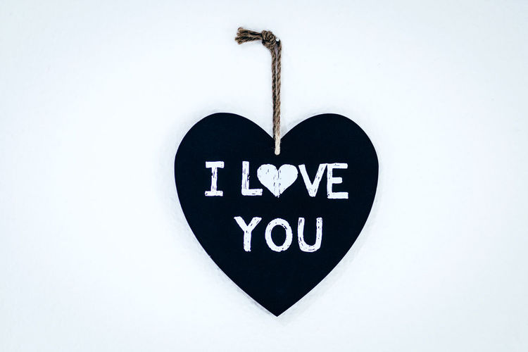 Close-up of heart shape sign hanging on white background