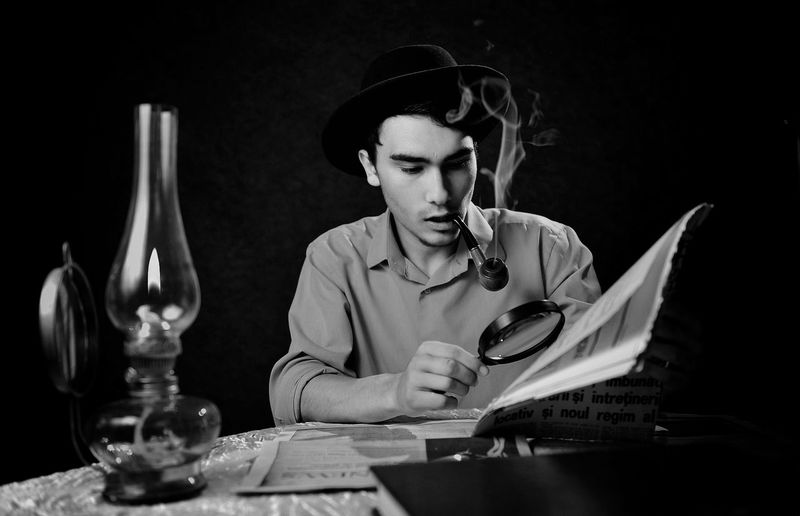 Young man smoking pipe while using magnifying glass at table