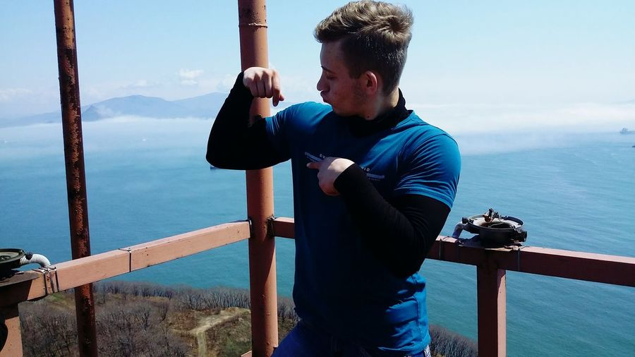 Man flexing muscles while standing by railing against sky