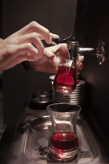 Cropped Hands Of Man Filling Water In Glass At Darkroom