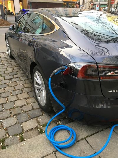 Tesla Elektroauto beim Aufladen an Zapfsäule mit Strom Energy Supply Energy Industry Energy Transportation Car Electric Car Mode Of Transportation Transportation Car Motor Vehicle Land Vehicle City Street Outdoors Stationary