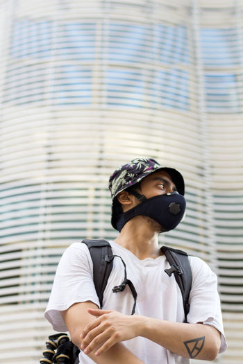 Man wearing a face mask to avoid coronavirus infection looking side ways while wearing a bucket cap.