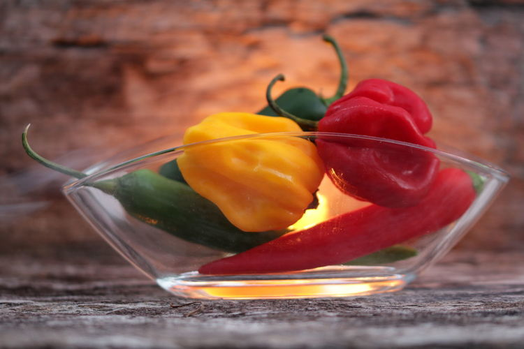 Close-up of chili peppers and bell peppers in bowl on table