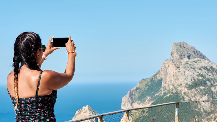 Rear view of man photographing on mobile phone against sea