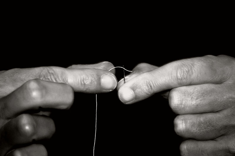 Cropped Hands Threading Sewing Needle Against Black Background