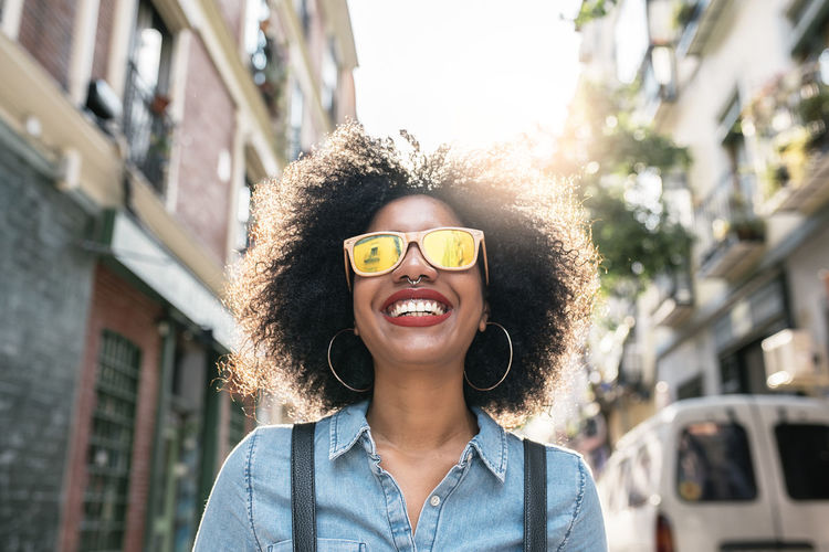 Portrait of beautiful afro american woman in the street Adult African Afro Casual City City Life Copy Space Fashion Happy Lifestyle Looking At Camera Positive Woman Black Denim Ethnic Female Girl Model Outdoors People Portrait Smiling Sunglasses Urban