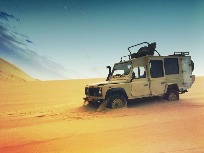 Sports Utility Vehicle On Desert Against Sky