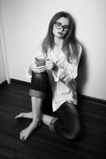 Portrait of smiling woman sitting on floor at home