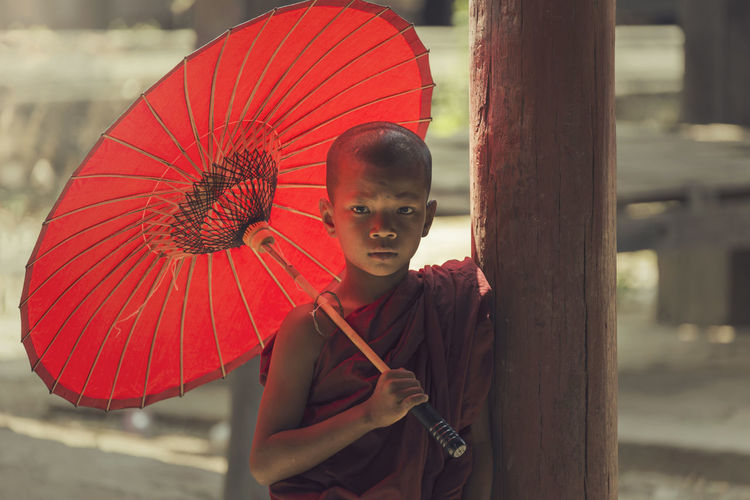 Portrait Of Monk Holding Red Umbrella By Wooden Column