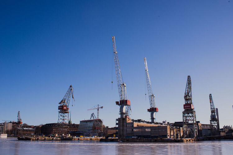 Cranes at commercial dock against clear blue sky