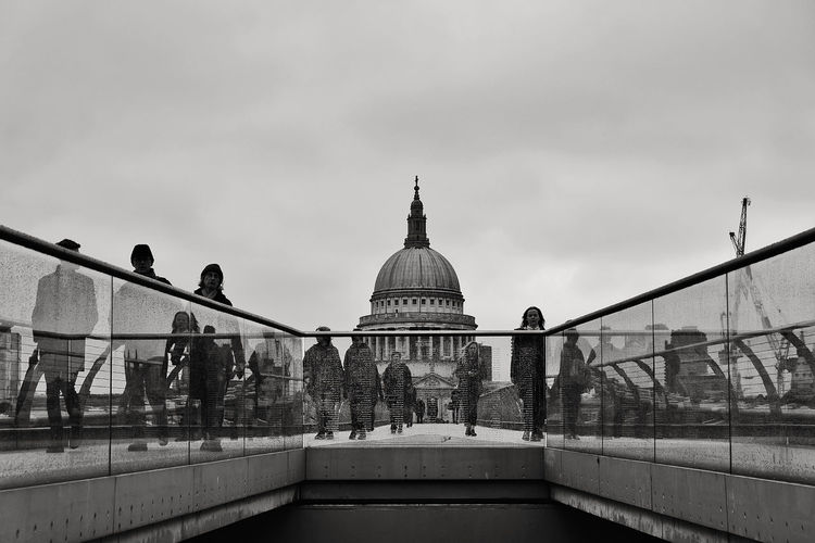People Walking On Bridge Against St Paul Cathedral
