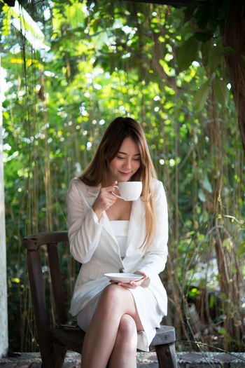 Businesswoman drinking coffee while sitting on chair against trees