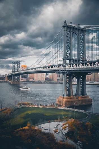 Manhattan bridge over east river against cloudy sky in city