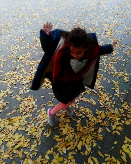 Full length of happy girl with autumn leaves in water