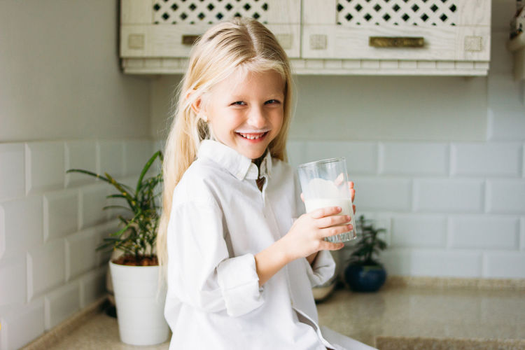 Portrait of smiling girl holding milk in glass