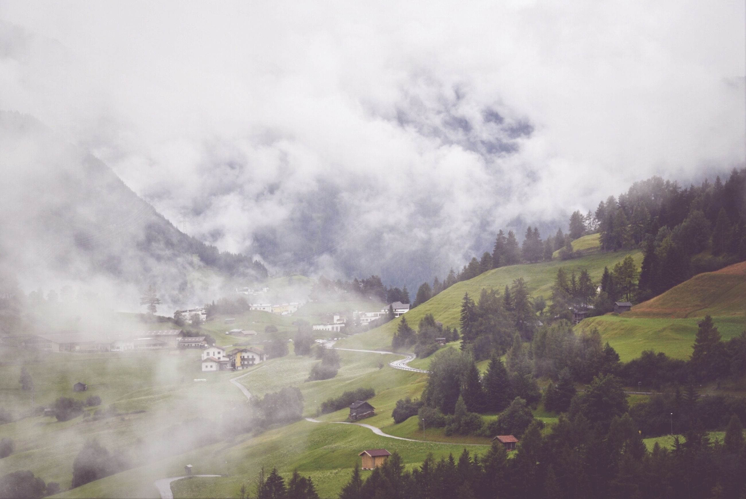 landscape, mountain, sky, scenics, transportation, tranquil scene, tree, tranquility, weather, beauty in nature, nature, cloud - sky, fog, green color, non-urban scene, field, road, cloudy, day, high angle view