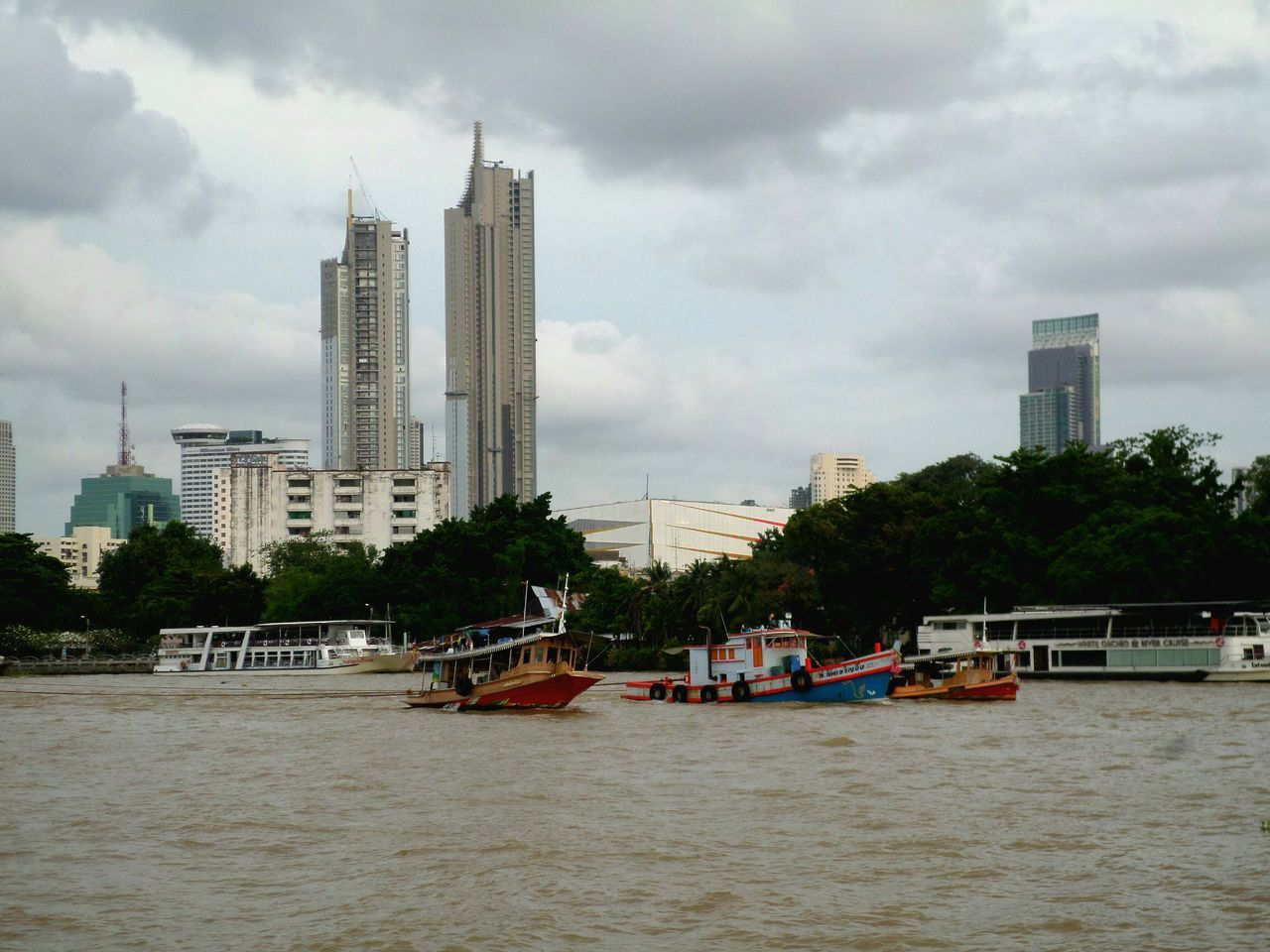 BOATS IN RIVER BY BUILDINGS AGAINST SKY