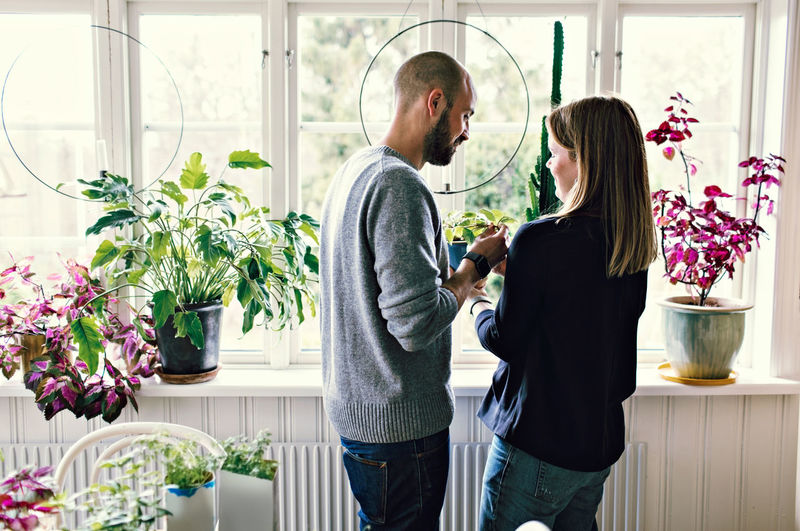 Man and woman standing by potted plants