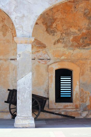 Terracotta and blue Abandoned Arch Architecture Bad Condition Brick Wall Building Built Structure Cart Ceiling Columns Damaged Deterioration Door Entrance Fort Geometry Indoors  Obsolete Ocean Old Old San Juan Orange Ruined San Juan PR Sancristobal Symmetry Terracotta Wall Wall - Building Feature Window Windows