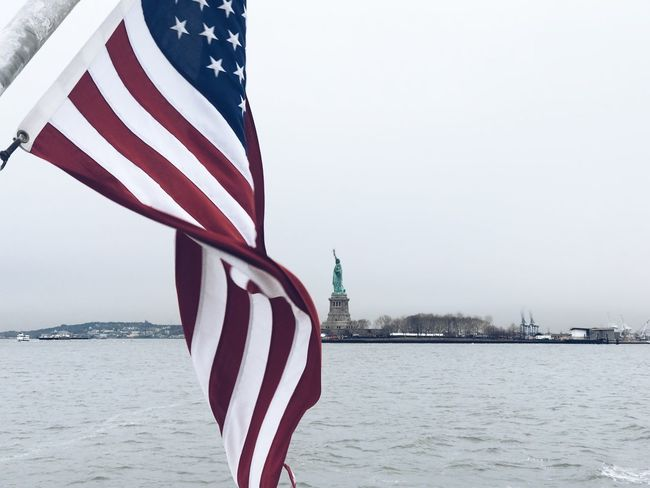 American Flag Statue Of Liberty Patriotism Flag Striped Stars And Stripes Water Independence No People Pride Sky Sea Day Outdoors Clear Sky Nature