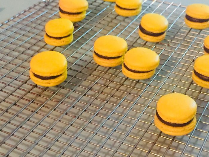 High angle view of yellow macaroons on metal grate