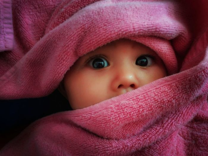 Close-Up Portrait Of Cute Baby Girl Wrapped In Towel