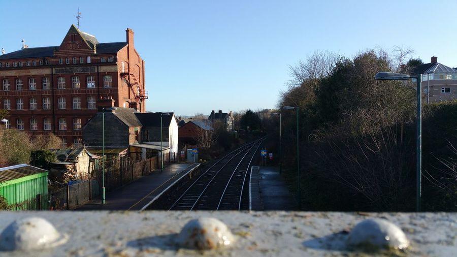 Railroad tracks amidst buildings against clear sky